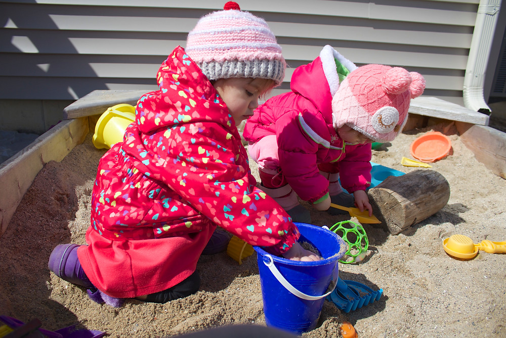 Blue Sky Daycare children playing in the sandbox outside