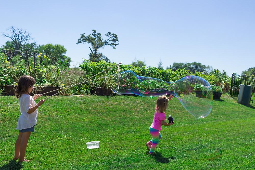 Blue Sky Daycare children create enormous bubbles!