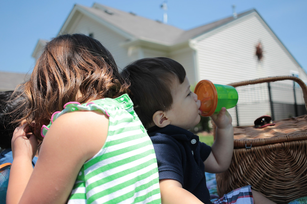 A Blue Sky Daycare child takes a cool drink on the very hot National Picnic Day.