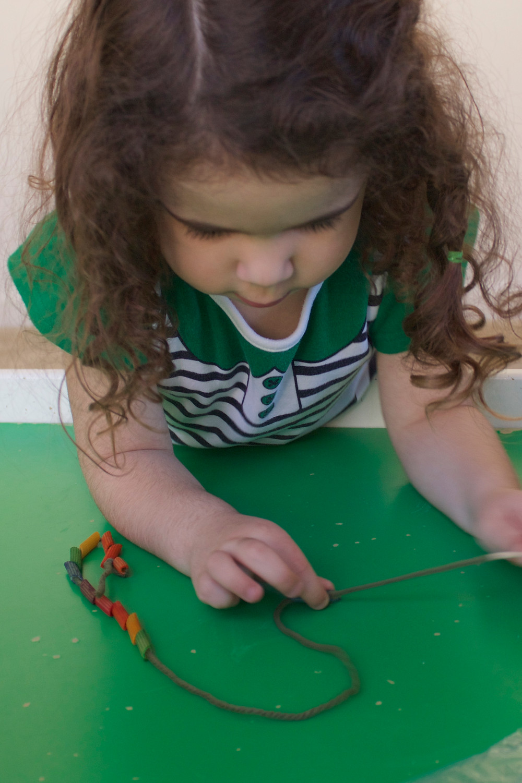 Blue Sky Daycare home daycare child uses fine motor skills to make a pasta neckace