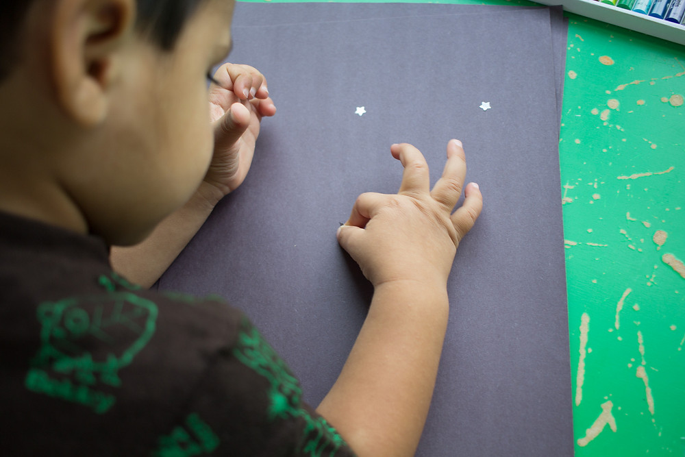 A child makes star-themed artwork at Blue Sky Daycare