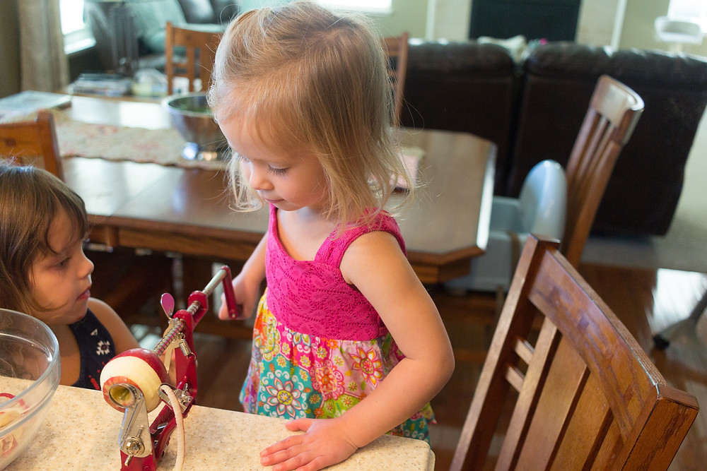 A Blue Sky Daycare child helps make applesauce from fresh-picked apples.