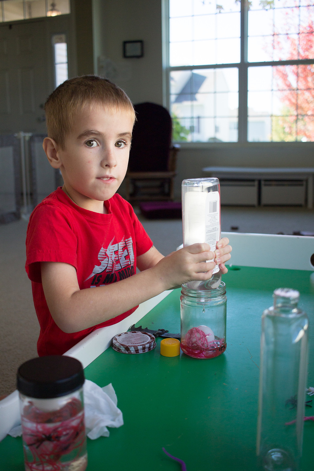 A Blue Sky Daycare child prepares a creepy look-and-find jar during craft time