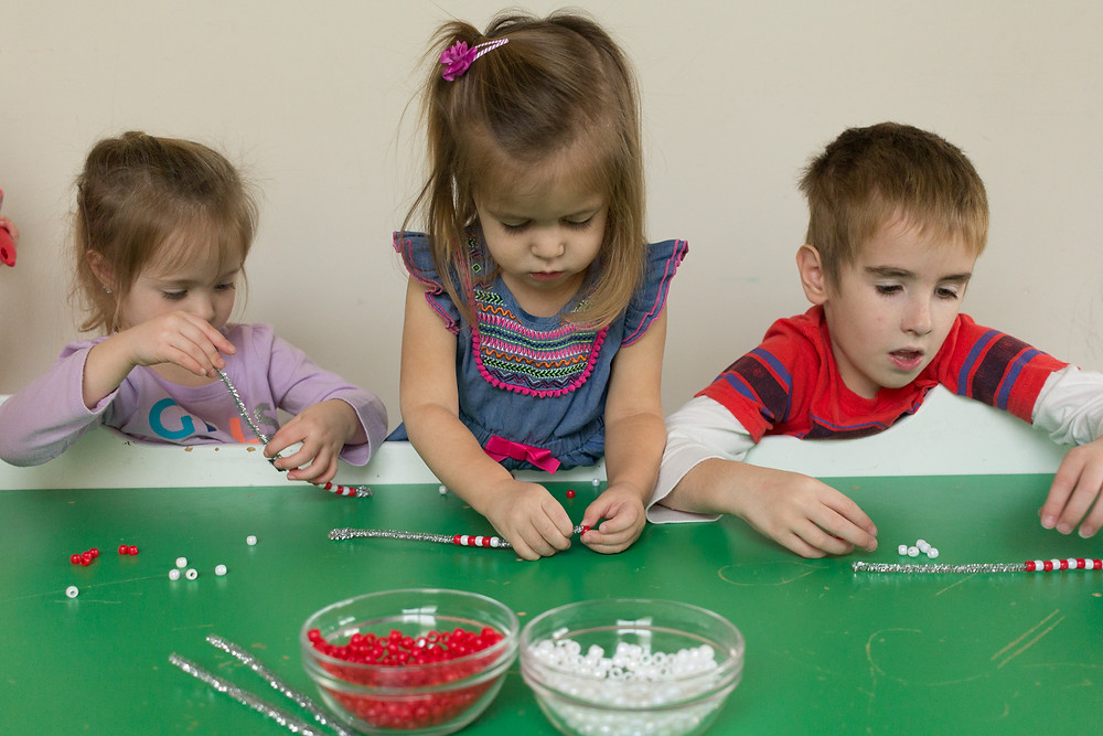 Blue Sky Daycare children make candy cane ornaments with beads and pipe cleaners