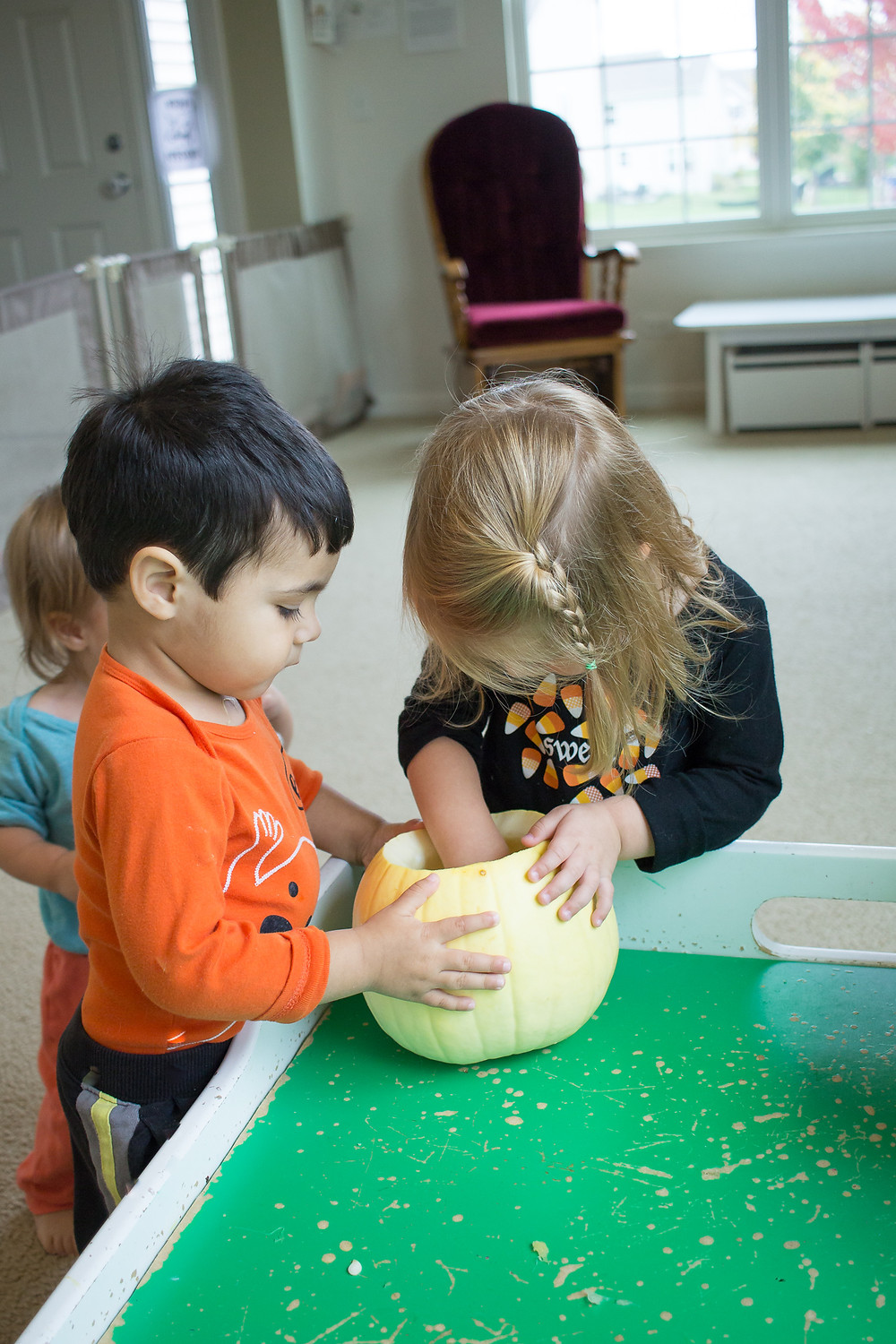 Pumpkin inspection- the Blue Sky Daycare kids help carve a Halloween jack-o-lantern.