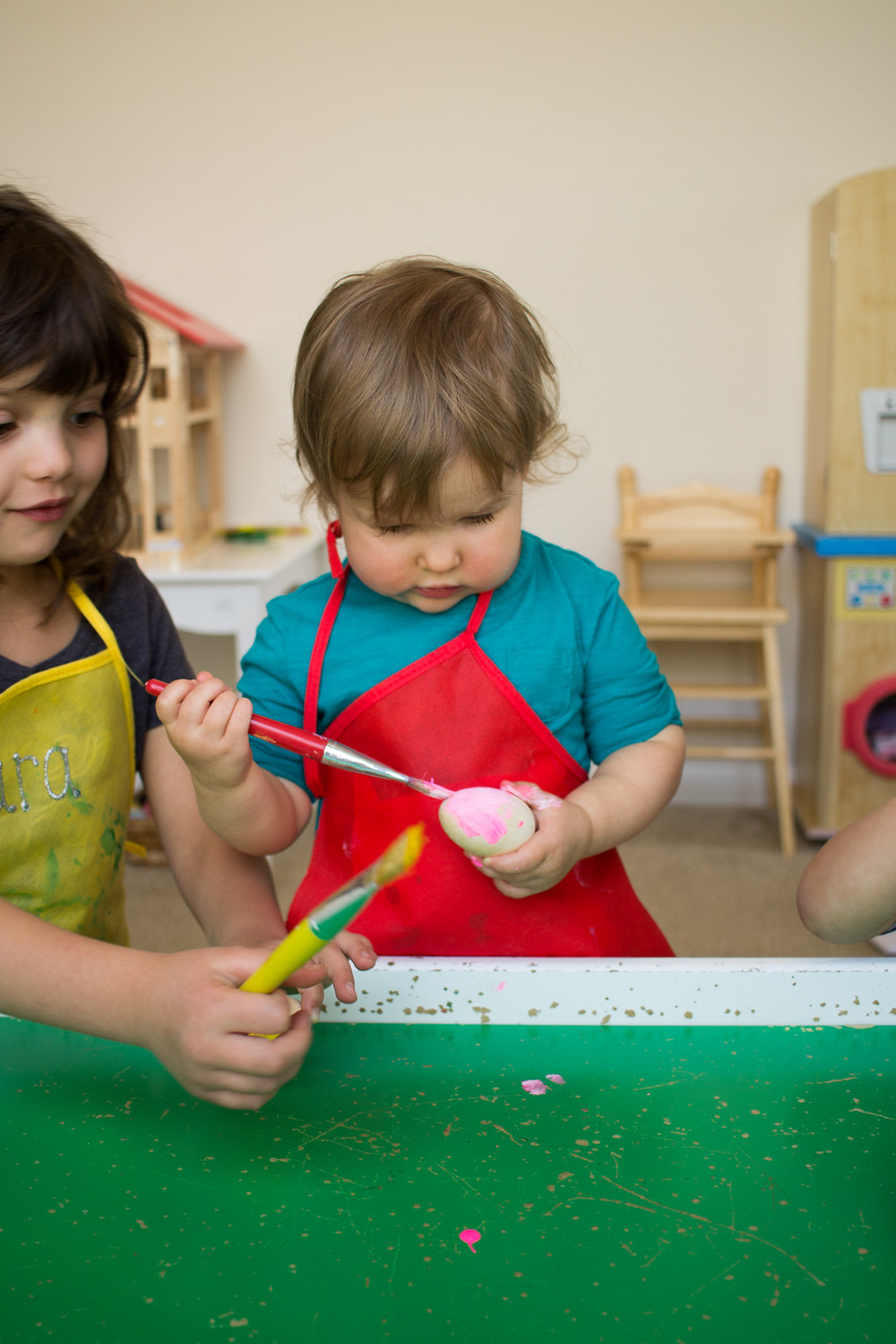 A BLue Sky Daycare child paints an Easter egg.