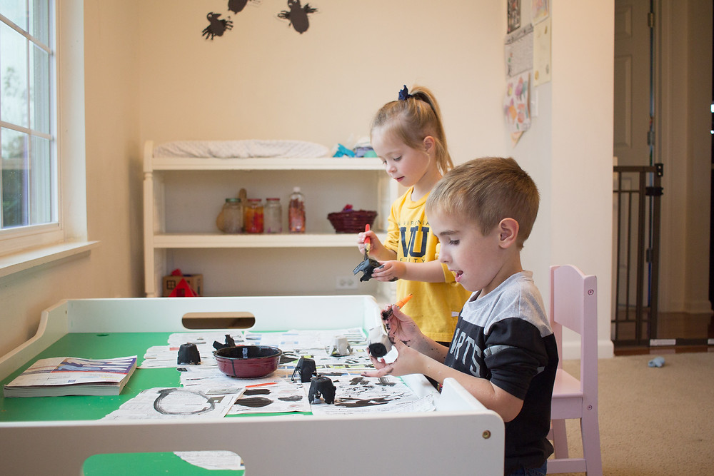 Blue Sky Daycare children paint egg cartons to make a Halloween spider craft.