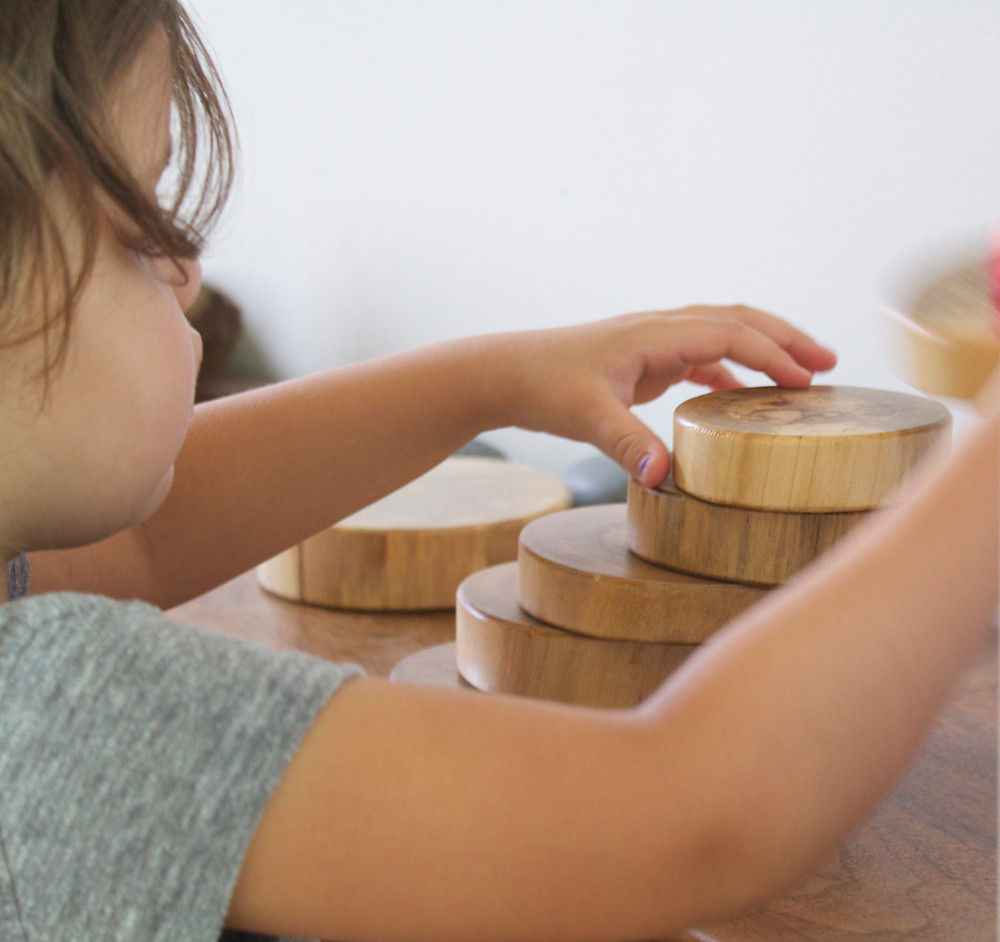 A child playing with handmade nature blocks at Blue Sky Daycare home daycare