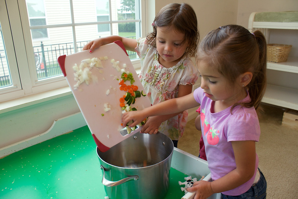 Blue Sky Daycare home daycare children adding vegetables to a pot of soup