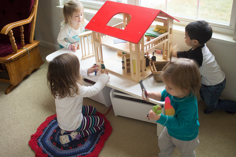 Blue Sky Daycare children enjoy their new dollhouse.