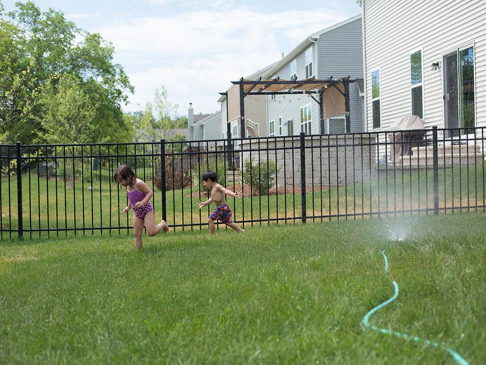 Children enjoy playing under the sprinkler at Blue Sky Daycare