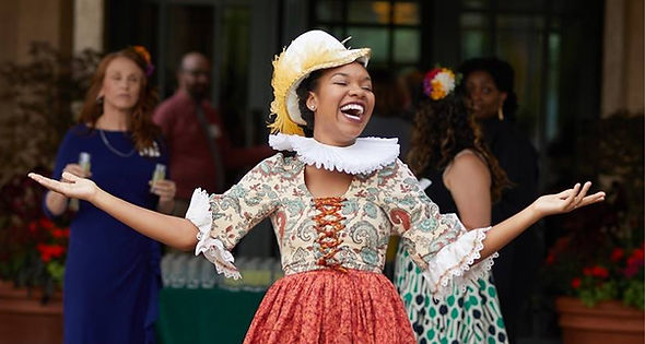 An actor performing in Elizabethan period dress with arms out and smiling.