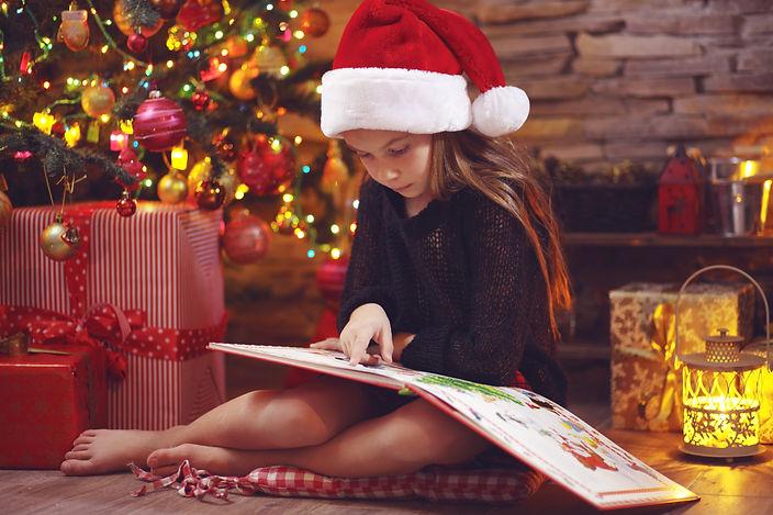 Child sitting near Christmas tree at nig