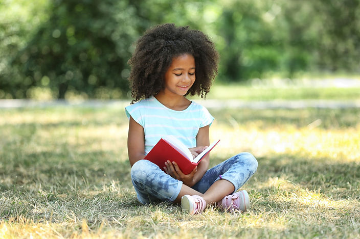Cute girl reading book on green grass.jp