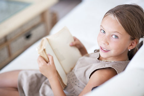Portrait of 7 years old child reading bo