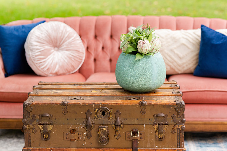 Pink vintage couch rental with pillows and a wooden trunk ottoman.