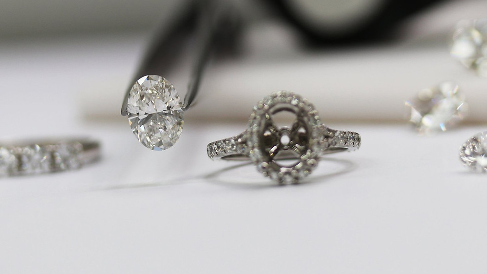 An oval diamond and a diamond engagement semi-mount surrounded by loose diamonds.