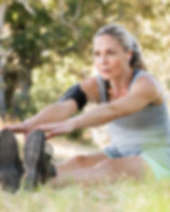 Senior woman exercising in park while li