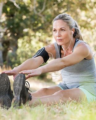 Senior woman exercising in park while li