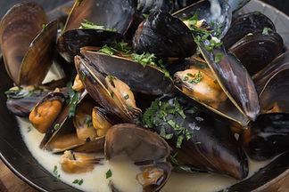 seafood mussels on pan with cream sauce.