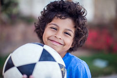 Smiling kid boy in blue t-shirt holding