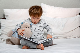 Little cute boy in pajamas reading a toy