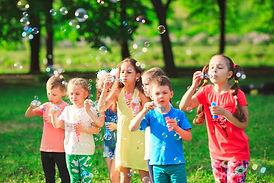 Group of children blowing soap bubbles.j