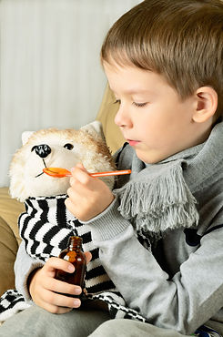 little boy feeds medicinal syrup the toy
