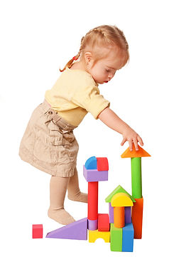 Baby girl building from toy blocks. Isol