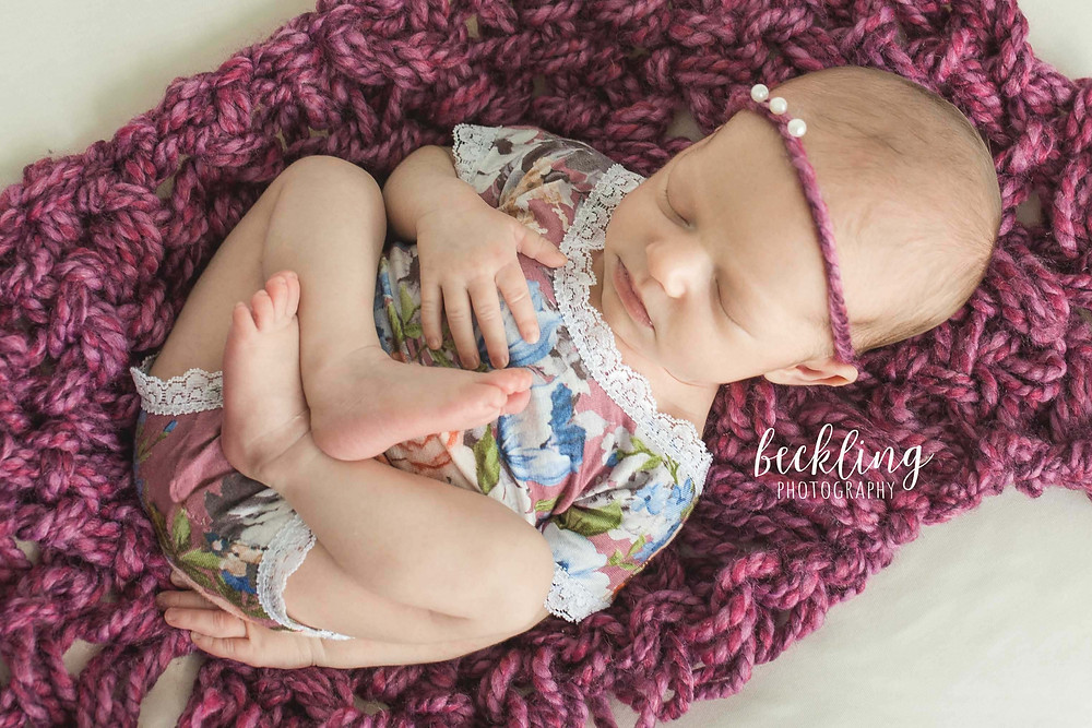 Beckling Photography | Savannah Newborn Photographer | Newborn girl with floral romper and magenta bump blanket