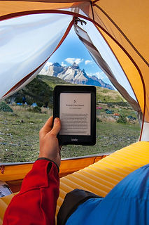 Picture of someone holding a digital device while camping under a tent in the mountains