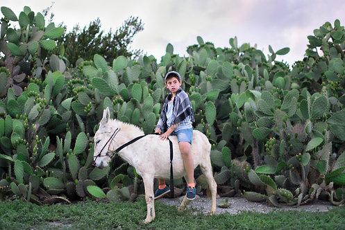 Uriya rides a donkey in Zaid Hills, Israel, 2016