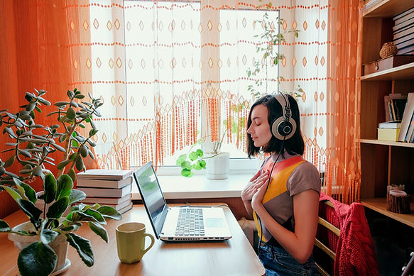 Female in headphones sits at front of laptop and breathing. Online audio meditation concep