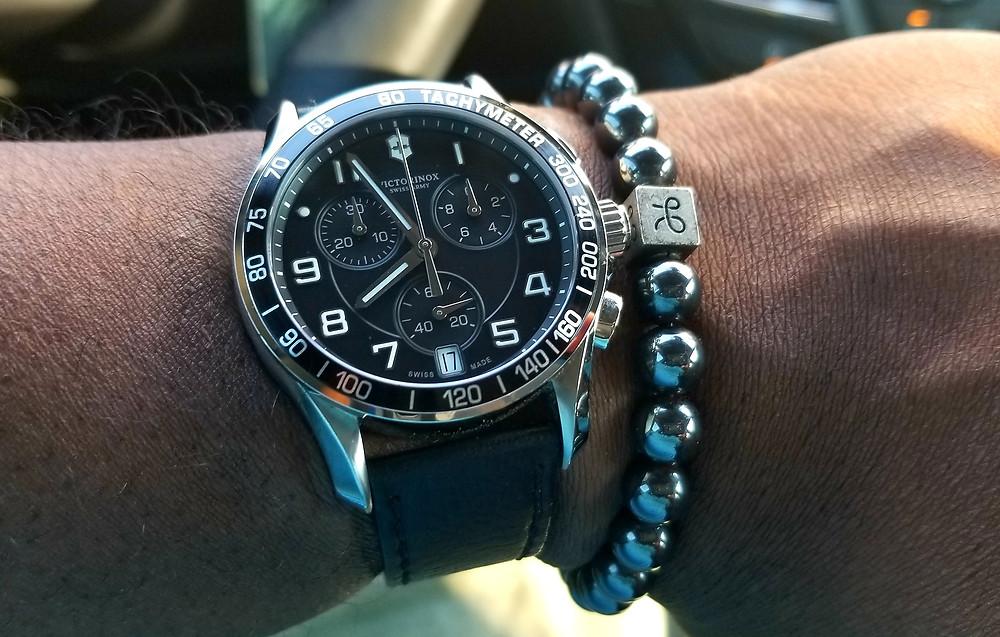 Victorinox, Chrono Classic timepiece, on black leather strap, accompanied by Aurum Brothers minimal hematite beaded bracelet.