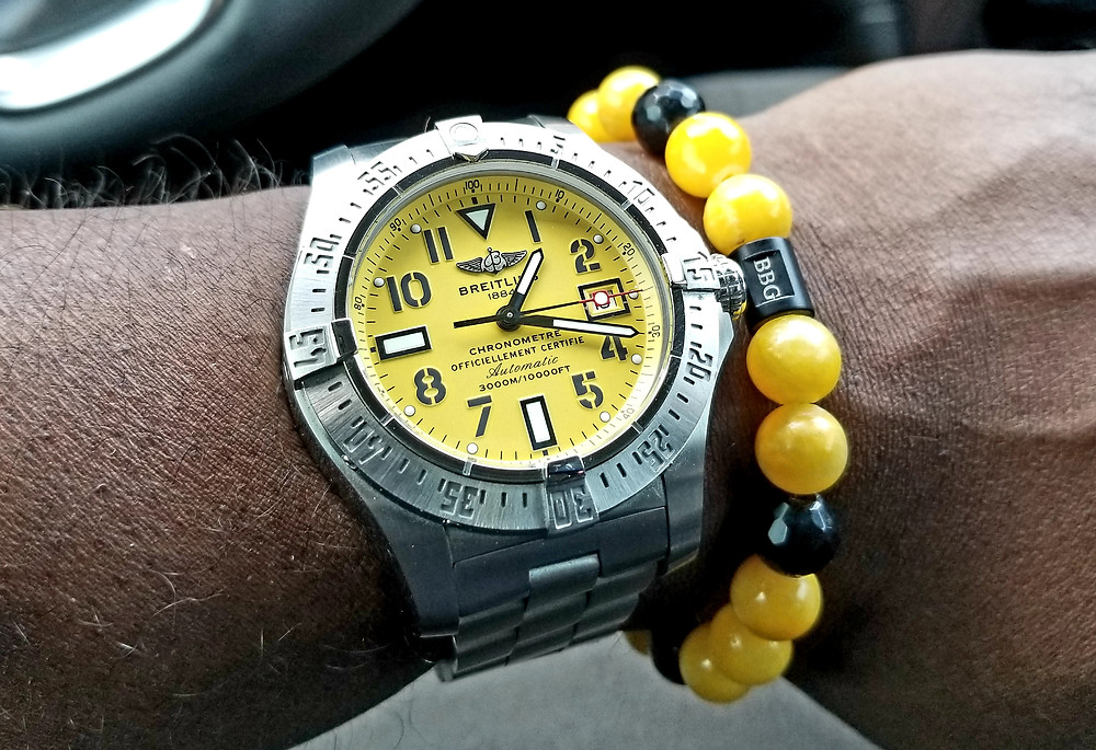 Wrist shot showing the Breitling, Aeromarine, Seawolf, on a bracelet, accompanied by yellow and black Beads by Gonzo beaded bracelet.