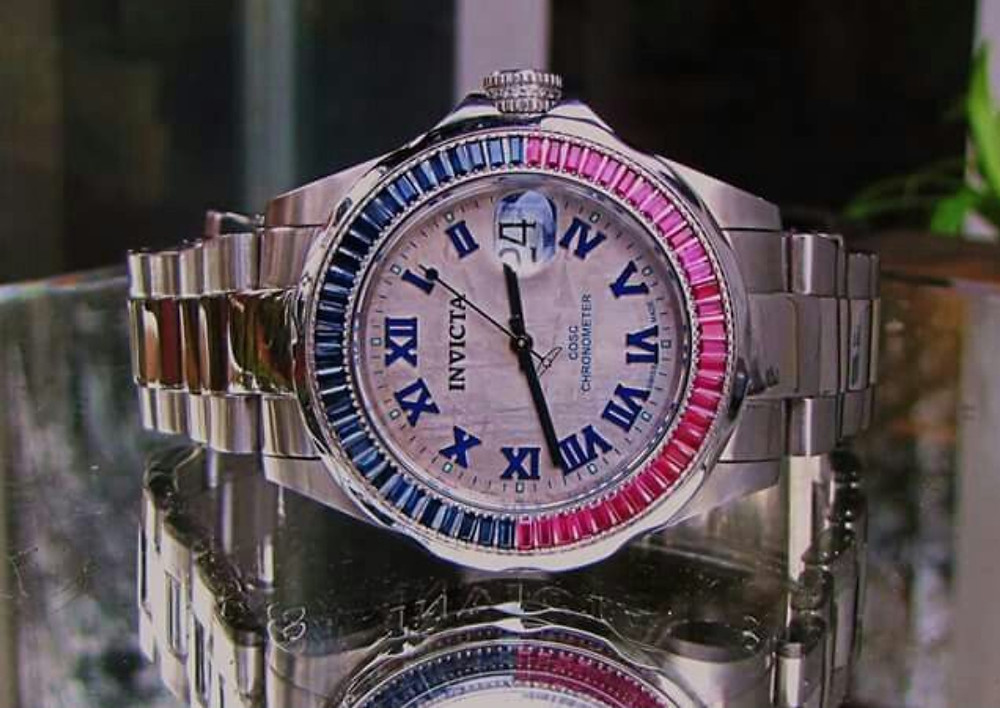Watch dial of the Invicta COSC Pro Diver showing ruby and sapphire gemstones on bezel, and meteorite dial.