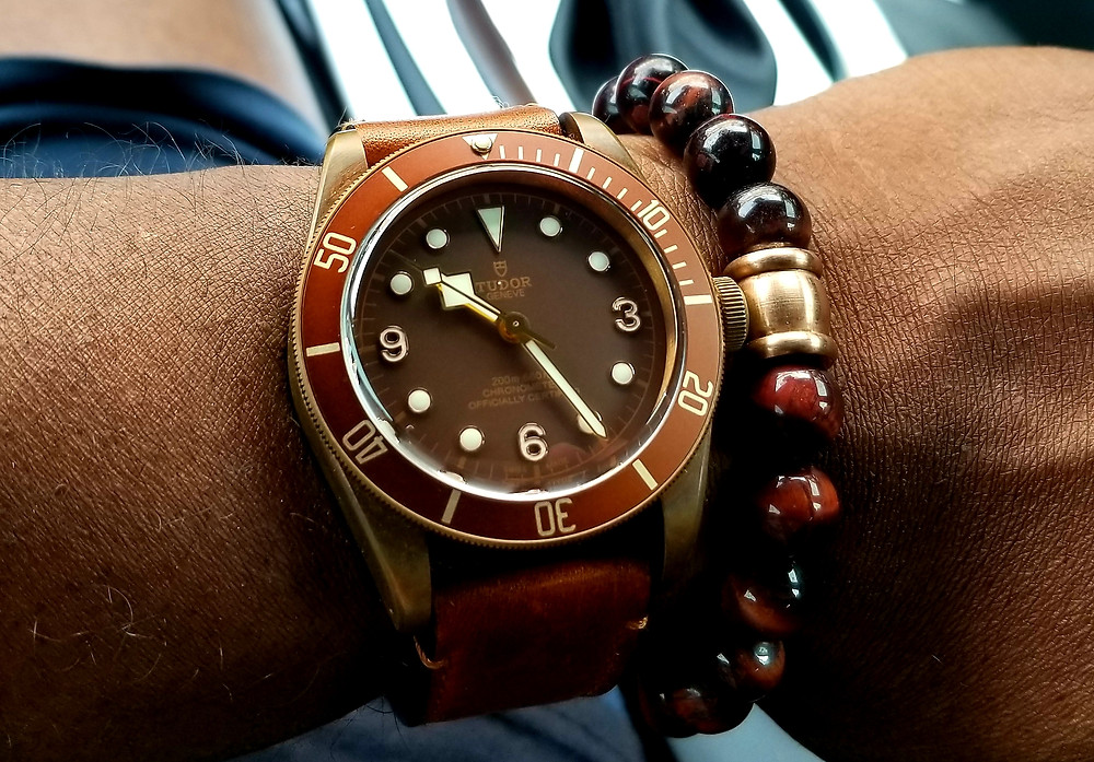 WOTD wrist shot showing Tudor, Heritage, Black Bay timepiece in bronze, with leather strap, accompanied by tiger's eye beaded bracelet.