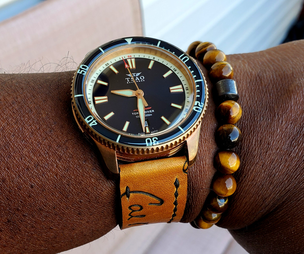 WOTD wrist-shot of the TSAO Baltimore, Torsk Diver - Bronze, Limited Edition.  Paired with a beaded bracelet, designed by Dorsal Bracelet Company, in color variation SoHo.