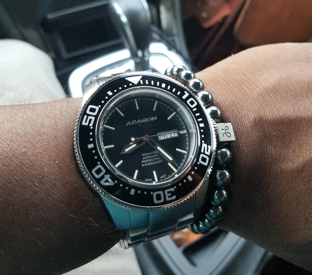 WOTD wrist shot of the Aragon, Divemaster T-100, XL, accompanied by minimalist, hematite bracelet from Aurum Brothers.