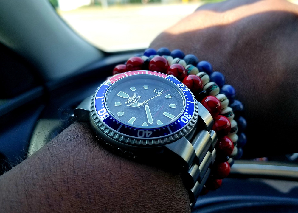 "Wrist-shot showing Invicta ""Scooby"" Pro Diver accessorized with 3 beaded bracelets, 1 red, 1 white, and 1 blue."