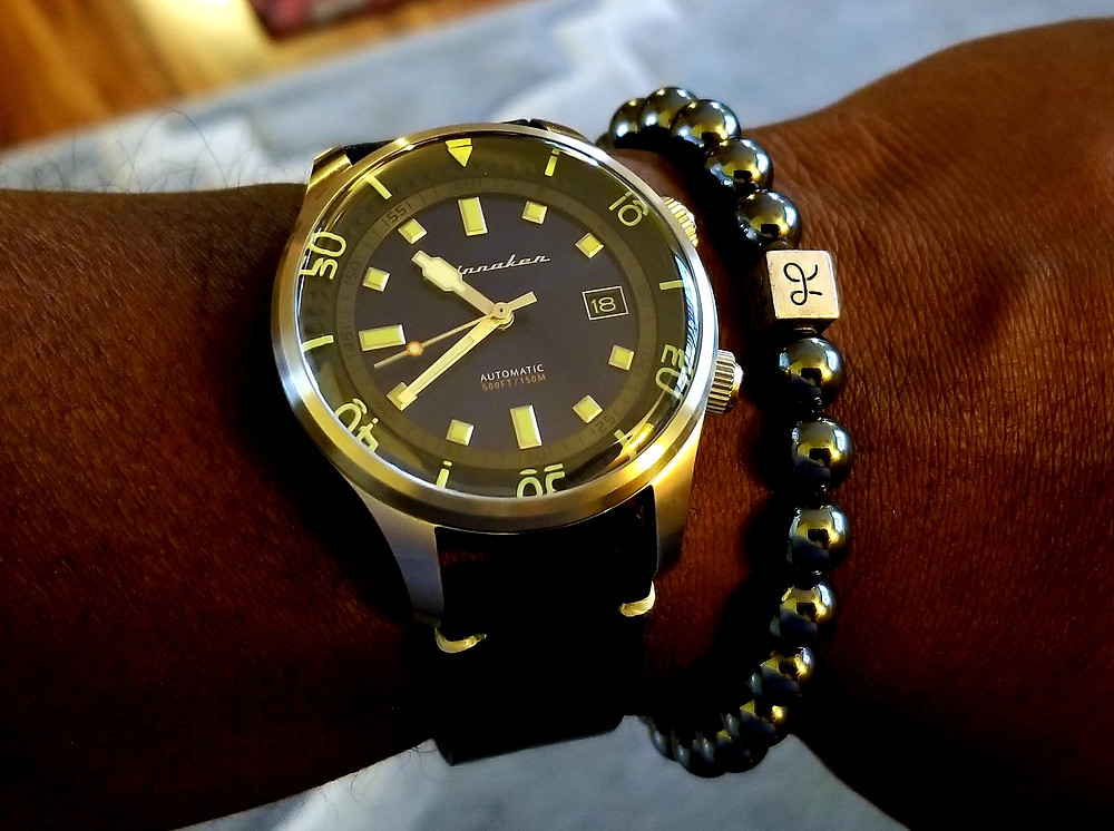 WOTD Wrist-Shot showing the Spinnaker, Bradner, Vintage, Compressor-Style Dive Watch, accompanied by minimalist, hematite beaded bracelet from Aurum Brothers.