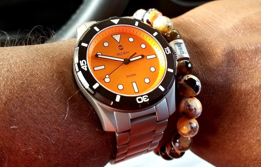 WOTD Wrist-Shot depicting the Helgray, TCD-01, Orange timepiece accompanied by a custom-made, Beads by Gonzo, beaded bracelet.