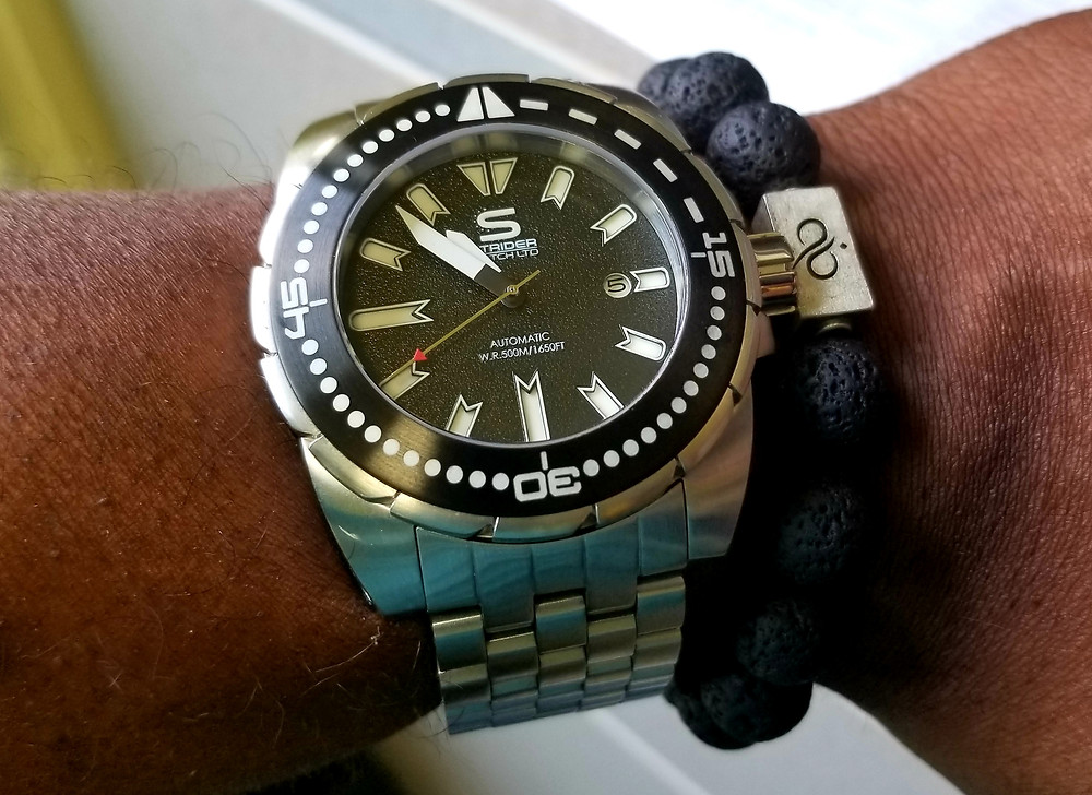 WOTD wrist shot showing Strider Hyperdive, Limited Edition timepiece, accessorized with Arum Brothers, Premium Lava beaded bracelet.