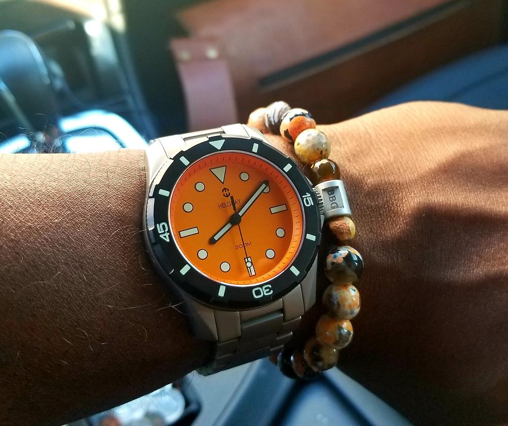 WOTD wrist shot showing the Helgray, TCD-01, Orange along-side a custom beaded bracelet made by Beads By Gonzo.