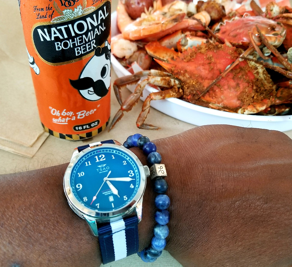 WOTD wrist-shot showing the Tsao Baltimore, Founder's, Limited Edition timepiece, accompanied by Aurum Brothers, sodalite beaded bracelet.  The watch is pictured with two iconic mainstays of Baltimore dining culture, Natty Boh beer, and Blue Crabs!