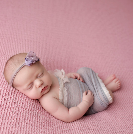 Newborn girl on pink