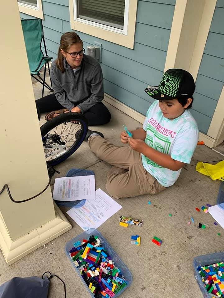 A child building legos with a young adult supervising