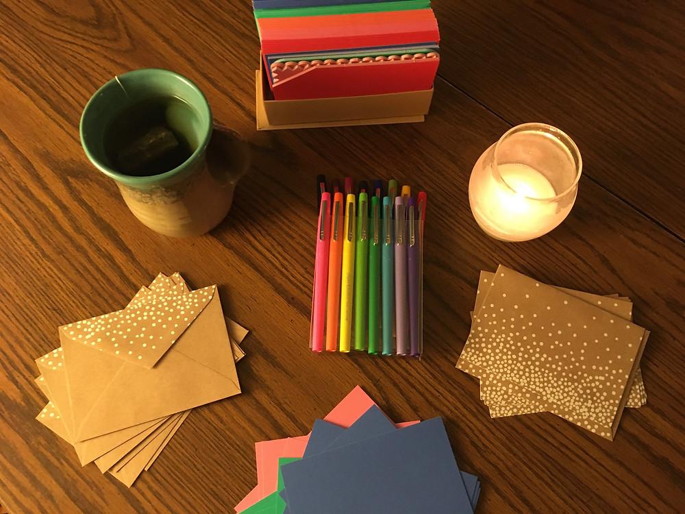 Stationery, pens, a mug of tea, and a candle
