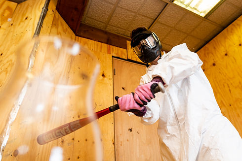 Rage room participant prepares to break a glass vase with a baseball bat