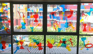 Bright coloured cut outs of musical instruments stuck on window. Through the window a block of flats is visible.